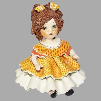"""Статуэтка """"Кукла сидящая с темными волосами в оранжевом платье"""""""